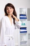 Lächelnde gesunde orientalische Frau im weißen Bademantel stockfotografie