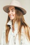 Lächelnde glückliche blonde Frau im hellrosa Hut Stockfotos