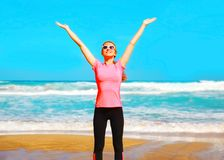 Lächelnde glückliche Frau der Eignung auf dem Strand nahe dem Meer Stockbild
