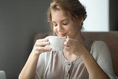 Lächelnde glückliche Frau, die aromatischen Kaffee mit geschlossenen Augen trinkt stockfoto