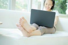 Lächelnde glückliche Frau, die auf dem Sofa und der Anwendung des Laptops sitzt Stockbild