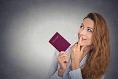 Lächelnde glückliche Frau, die den Pass schaut oben halten steht, vorstellend neues Leben Stockfotografie