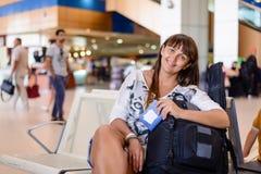 Lächelnde glückliche Frau in einem Flughafenabfertigungsgebäude lizenzfreie stockbilder