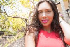 Lächelnde glückliche junge Frau in einem tropischen Garten Stockfotos
