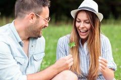Lächelnde glückliche junge Paare, die zusammen Zeit auf einem Picknick im Park verbringen lizenzfreies stockfoto