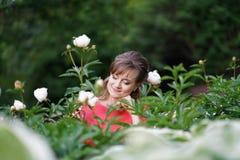 Lächelnde glückliche kaukasische erwachsene Frau, die in ihrem Garten mit blühenden Blumen sich entspannt stockfoto