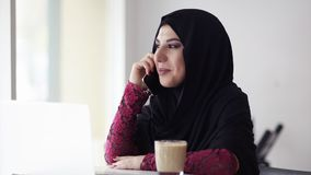 Lächelnde glückliche moslemische Frau der Junge im hijab, das im Café mit Tasse Kaffee sitzt und an ihrem Handy spricht modern stock video
