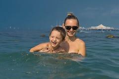 Lächelnde glückliche Mutter und Sohn, die auf der Welle im Meer in t spielen Stockfoto