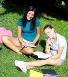 Lächelnde glückliche Studentinnen im College mit Büchern stockbild