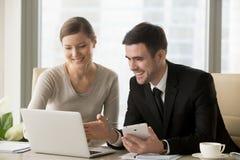 Lächelnde glückliche Wirtschaftler, die intelligente Geräte für bewegliches busi verwenden lizenzfreie stockfotografie