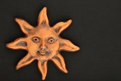Lächelnde glasig-glänzende keramische Sonnenandenken lokalisiert auf Schwarzem Stockfoto