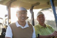 Lächelnde Golfspielerfreunde, die im Golfbuggy sitzen lizenzfreies stockfoto