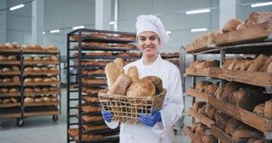 Lächelnde große charismatische reife Bäckerfrau, die einen Weinlesekorb mit organischem Brot hält und gerade zu schaut stock footage