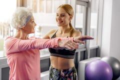 Lächelnde Großmutter, die Trainer in der Turnhalle beschäftigt lizenzfreie stockfotos