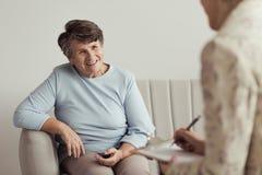 Lächelnde Großmutter und Finanzratgeber lizenzfreie stockbilder
