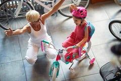 Lächelnde Großmutter und Mädchen, die Fahrrad und Sturzhelme im Fahrradgeschäft wählen stockfotografie