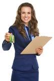 Lächelnde Grundstücksmaklerfrau, die mit Klemmbrettschlüsseln gibt Lizenzfreie Stockbilder