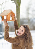 Lächelnde hängende Vogelzufuhr der jungen Frau auf Baum Stockbilder