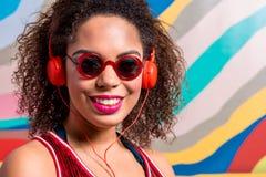 Lächelnde hörende Musik der Frau durch Kopfhörer Lizenzfreie Stockfotos