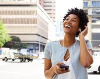 Lächelnde hörende Musik der jungen Frau auf Kopfhörern lizenzfreie stockfotos