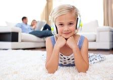 Lächelnde hörende Musik des Mädchens, die auf dem Fußboden liegt stockfotos