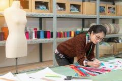 Lächelnde hübsche Designerfrau, die blauen Reißverschluss hält stockbilder
