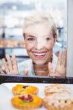 Lächelnde hübsche Frau, die eine Fruchttorte durch das Glas betrachtet Stockfotografie