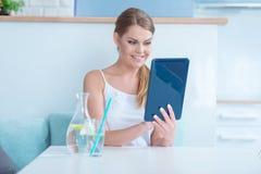 Lächelnde hübsche Frau, die ihren Tablettenschirm liest Stockfotografie