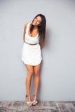Lächelnde hübsche Frau, die im modischen weißen Kleid steht Stockfotos