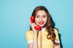 Lächelnde hübsche Frau im Kleid, das Retro- Telefonrohr hält lizenzfreie stockfotos