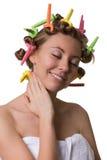 Lächelnde hübsche Frau mit geschlossenen Augen und Lockenwicklern auf Haar stockfoto