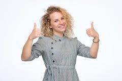 Lächelnde hübsche gelockte junge Frau, die Daumen herauf Sein glücklich, einen Job zu übernehmen zeigt lizenzfreie stockbilder