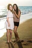 Lächelnde hübsche Mädchen am Strand während des Sonnenuntergangs Stockfotos