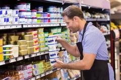 Lächelnde hübsche nehmende Milchprodukte Stockfoto