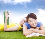 Lächelnde hübsche Studenten, die auf der Wiese mit Büchern liegen Stockfotos