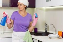 Lächelnde Hausfrau, die Reinigungsmittel und Seife hält stockbilder