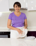 Lächelnde Hausfrau, die weg von den Platten in der Küche trocknet Stockfotos
