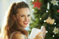 Lächelnde Hausfrau mit Notizbuch und Stift nahe Weihnachtsbaum lizenzfreies stockfoto