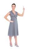 Lächelnde herrliche Frau im noblen Kleid ihren Finger oben zeigend Stockbild
