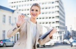 Lächelnde herrliche Geschäftsfrau, die das Tabletten-PC-Wellenartig bewegen hält Lizenzfreie Stockfotografie