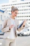 Lächelnde herrliche Geschäftsfrau, die Tabletten-PC verwendet Lizenzfreie Stockbilder