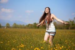 Lächelnde Hippie auf dem Sommerblumengebiet lizenzfreie stockfotografie