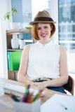 lächelnde Hippie-Geschäftsfrau, die einen Trilby trägt Stockfotos