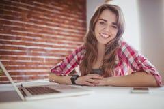 Lächelnde Hippie-Geschäftsfrau, welche die Kamera betrachtet Lizenzfreies Stockfoto