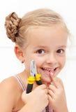 Lächelnde Holding des kleinen Mädchens ihr fehlender Zahn Lizenzfreie Stockfotos
