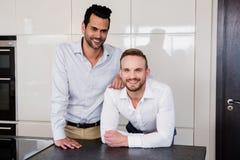 Lächelnde homosexuelle Paare in der Küche stockbilder
