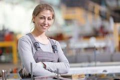 Lächelnde industrielle Arbeitnehmerin am Arbeitsplatz auf Fertigungswerkstatthintergrund Stockbilder