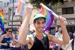 Lächelnde Jugend mit Regenbogenmarkierungsfahne an der Stolz-Parade TA Stockbild