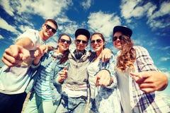 Lächelnde Jugendliche in der Sonnenbrille, die draußen hängt Stockfotos