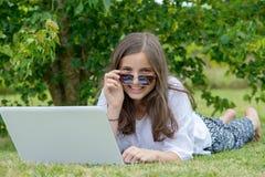 Lächelnde Jugendliche, die auf dem Gras unter Verwendung des Laptops liegt lizenzfreie stockbilder